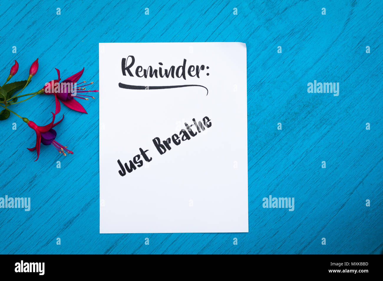 Reminder to Just Breathe still life motivational concept on white paper and blue table flat lay in vintage tones - Stock Image