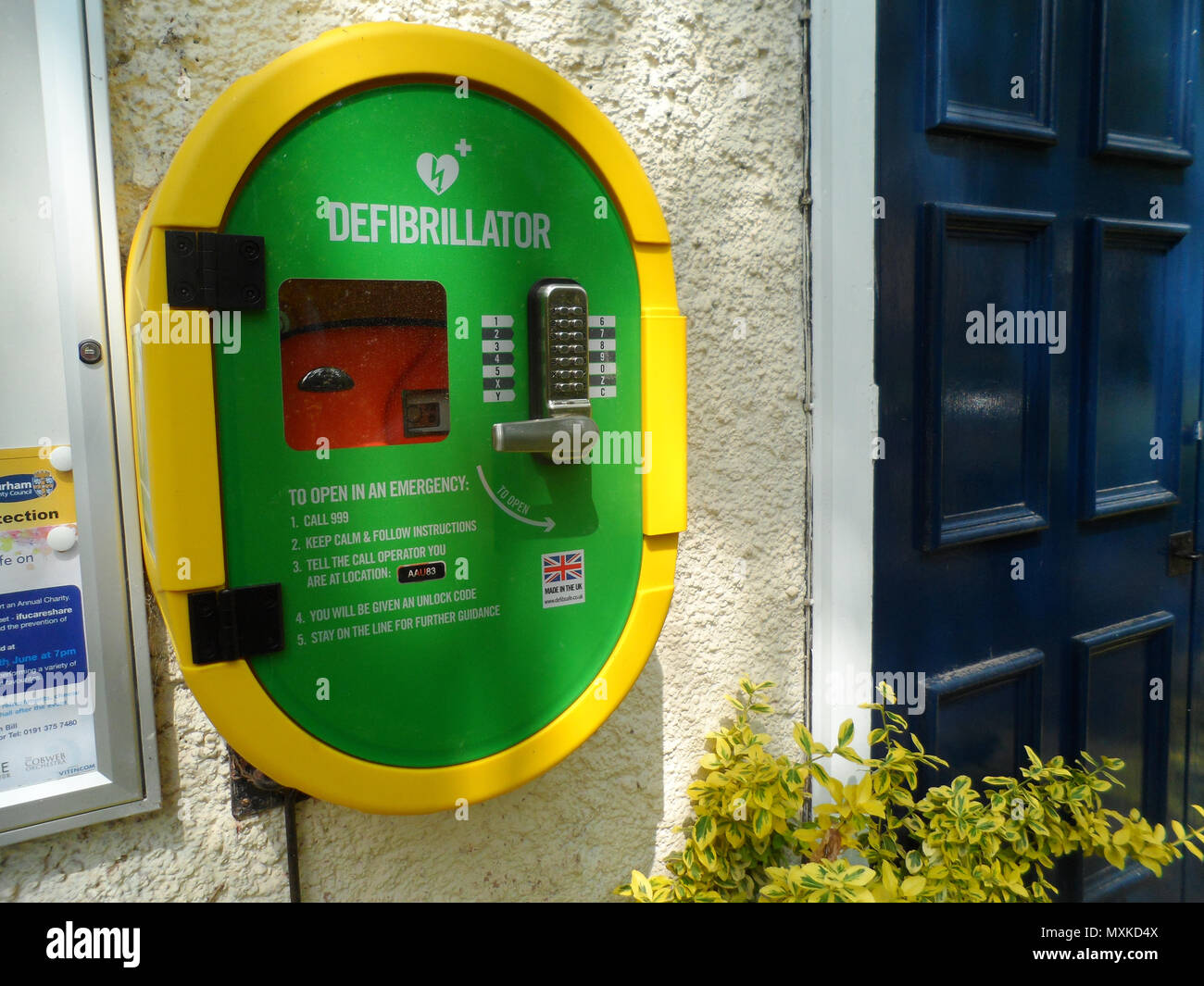 Public emergency defibrillator mounted on the wall of the community center at Shincliffe, County Durham, England. - Stock Image
