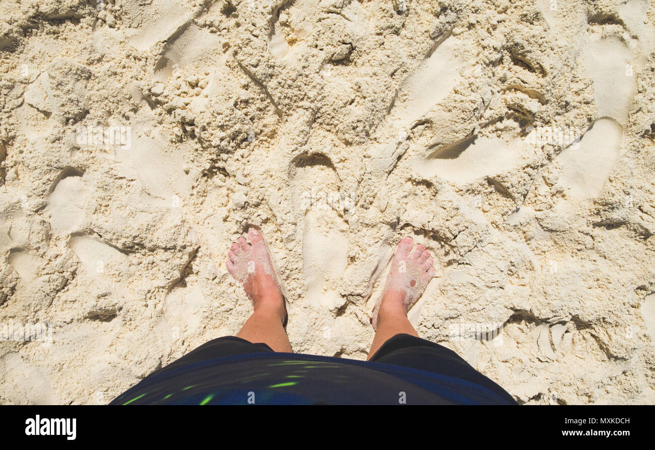 aerial view of barefoot with swimming suit stand on sand at sea beach in sunny day,summer vacation holiday lifestyle.Leave space on top for adding you - Stock Image