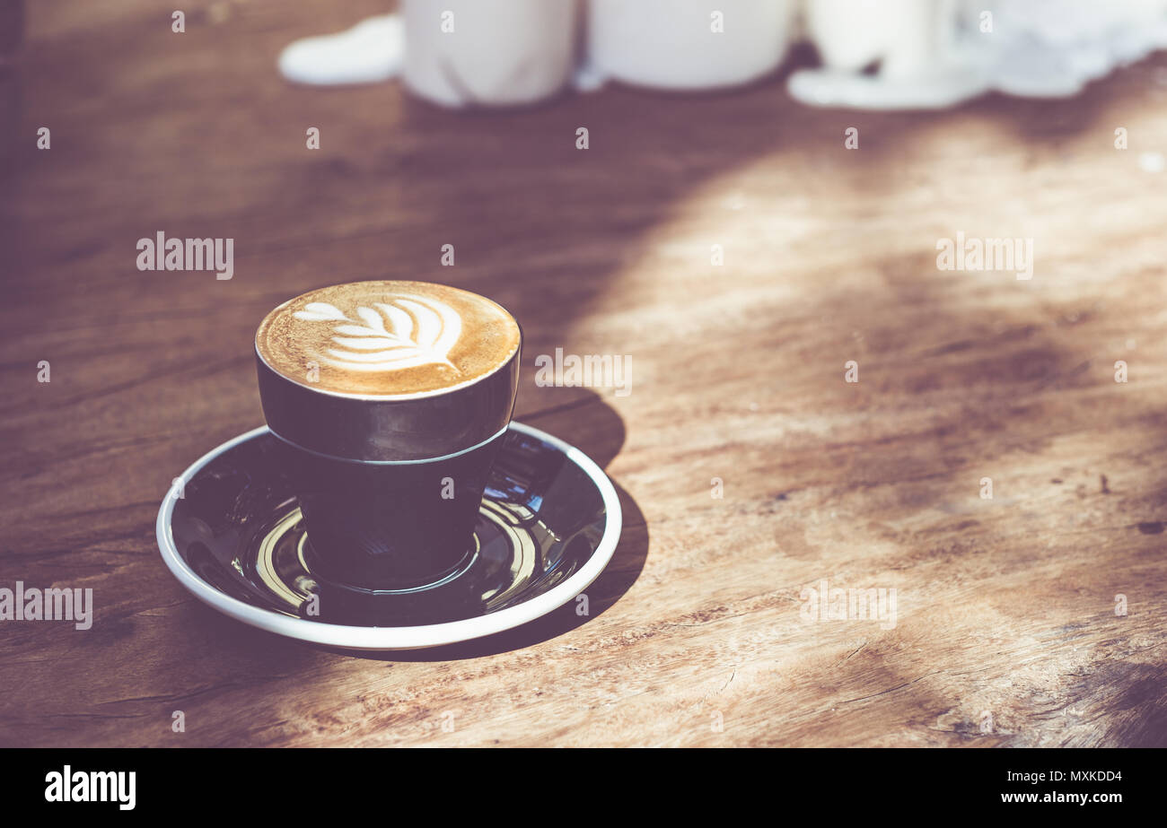 Close up hot black coffee cup with tree heart shape latte art milk foam on wood table near window with hard shadow sunlight at cafe restaurant.Leisure - Stock Image