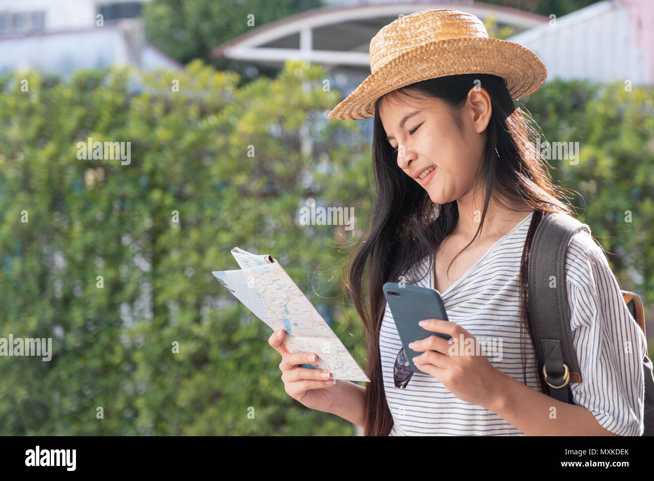 Asian woman traveler backpacker use map and mobile phone app to search for route location of place with gps on street in when travel in city,Technolog - Stock Image