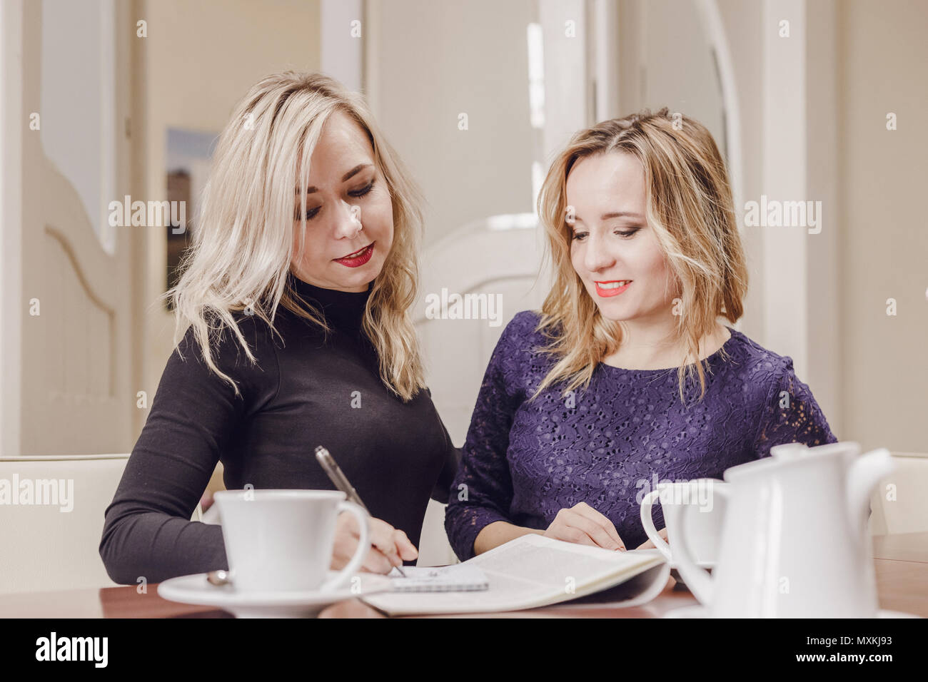 Two young women discussing documents and drinking tea at meeting in conference room - Stock Image
