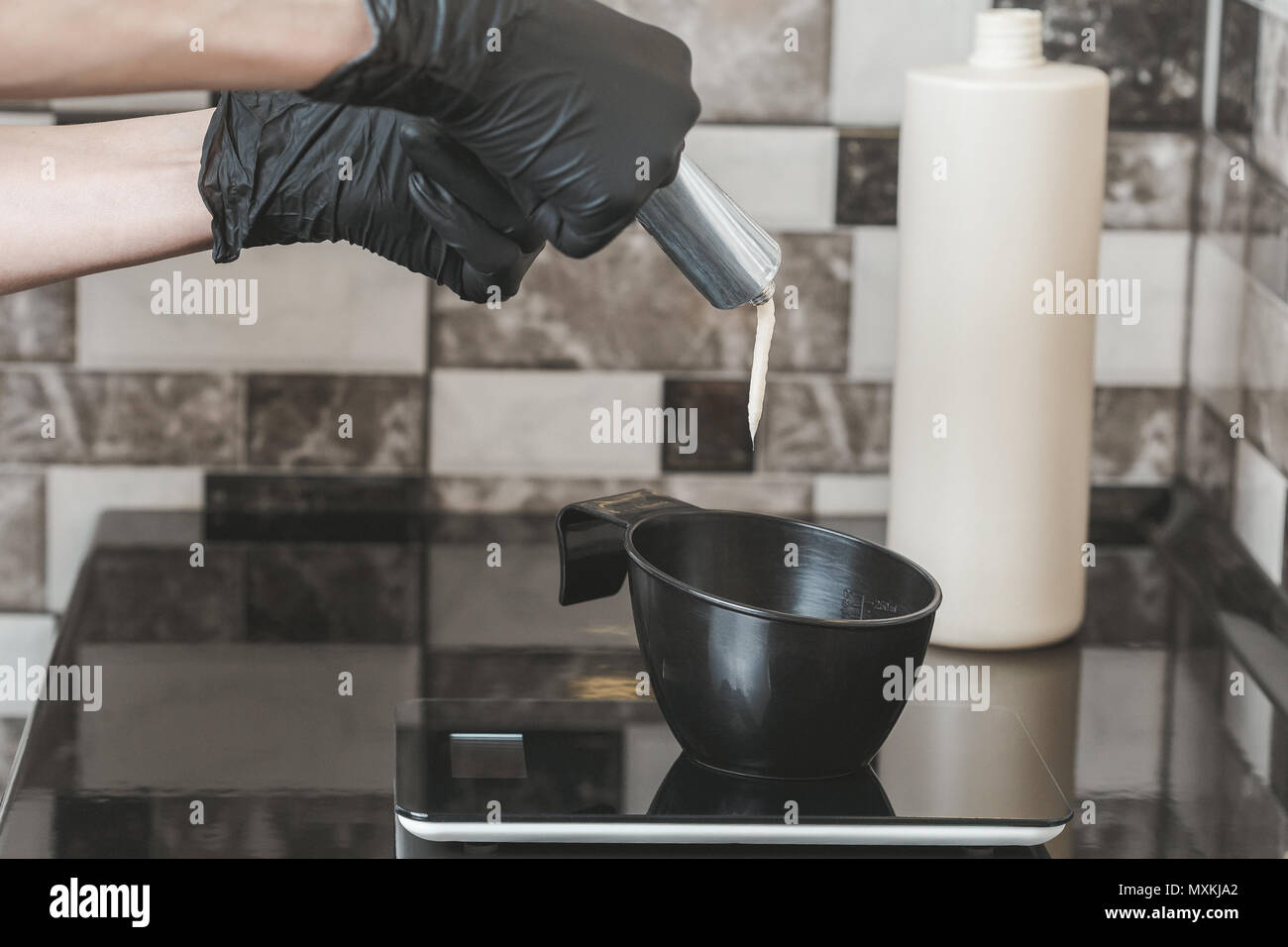 Stylist squeezing a hair dye in a bowl, Hair dyeing at home or in hairdresser salon concept - Stock Image