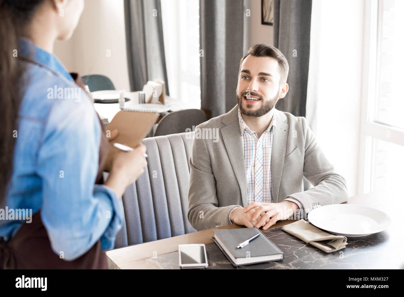 Positive businessman making order in restaurant - Stock Image