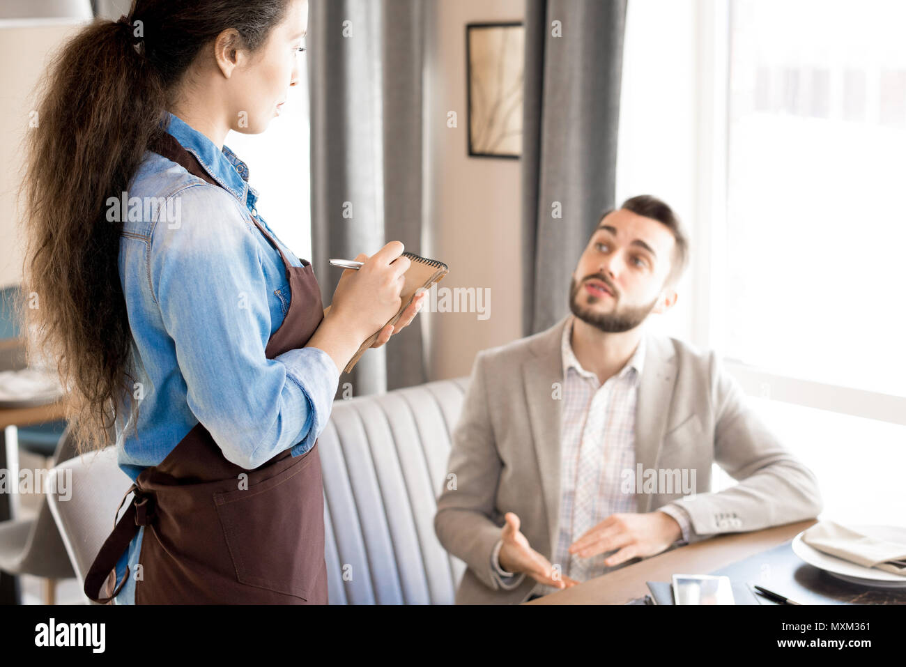 Man sharing his taste preference with waitress - Stock Image