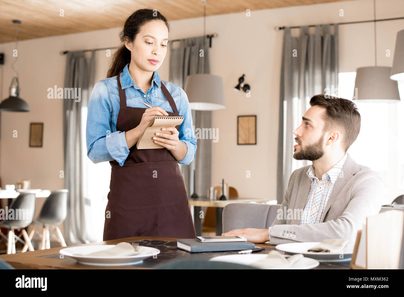 Serious waitress talking business lunch order - Stock Image