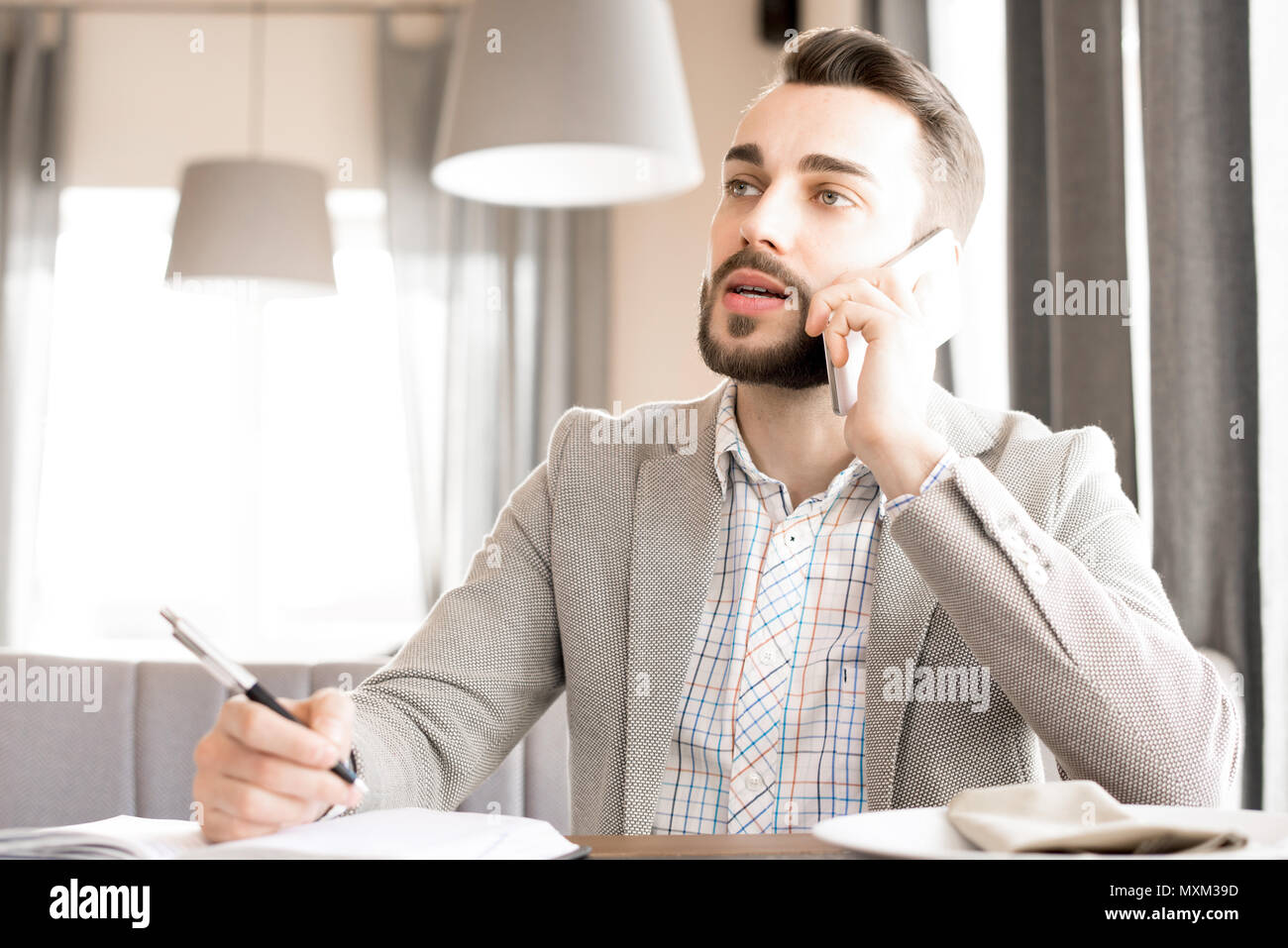 Modern bearded businessman working in cafe - Stock Image