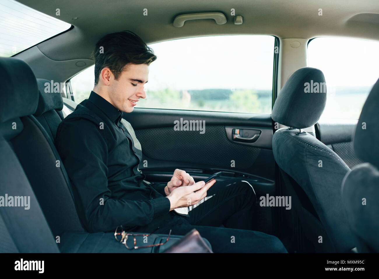 A young, handsome teenage boy sits on a passenger car seat and decides by phone - Stock Image