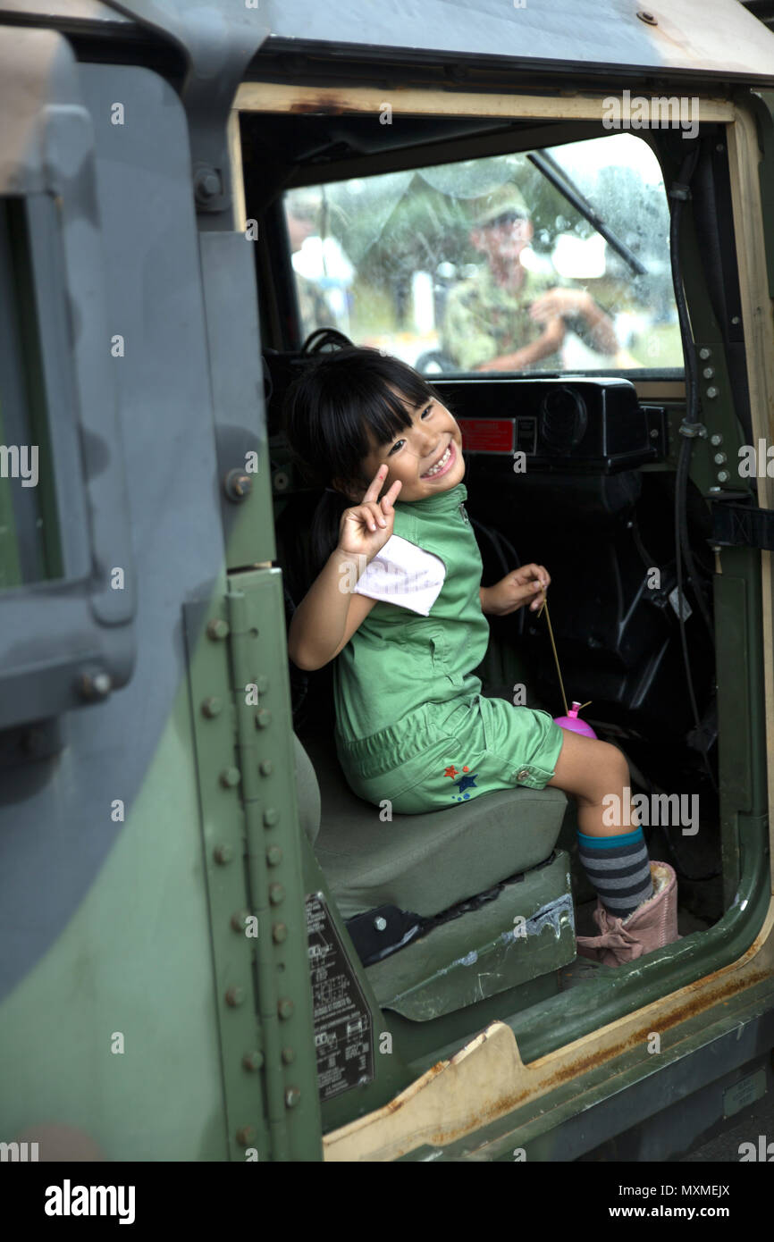 An Okinawa resident poses inside a Humvee Nov. 20, 2016 during the Japan Ground Self Defense Force Festival on Camp Naha, Okinawa, Japan. The festival celebrated the 6th anniversary of the 15th Brigade and the 44th anniversary of Camp Naha. Marines with Combat Assault Battalion, 3rd Marine Division, III Marine Expeditionary Force brought the Humvee, a Light Armored Vehicle and an Assault Amphibious Vehicle for display. Attendees of the festival were able to take photos with the Marines and their vehicles. (U.S. Marine Corps photo by Cpl. Jessica Collins) Stock Photo