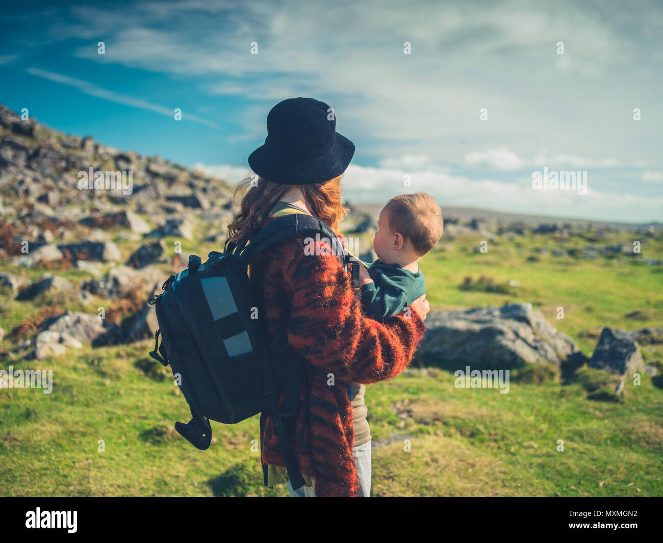 A young mother with a baby and a big bacpack is trekking through the wilderness - Stock Image