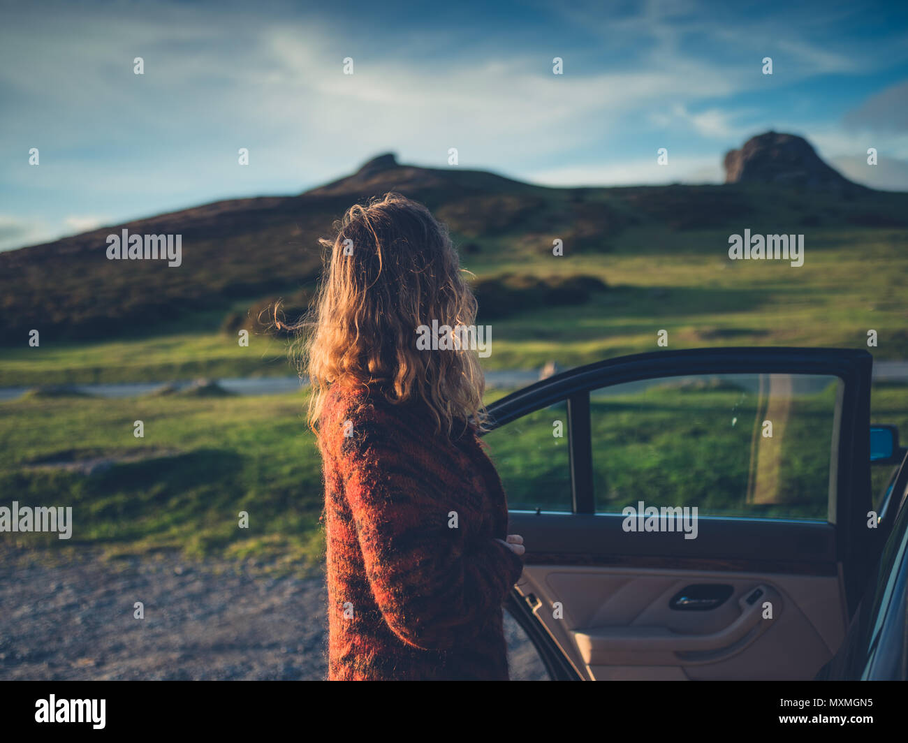 A young woman is opening the door of her car in the wilderness at sunset - Stock Image