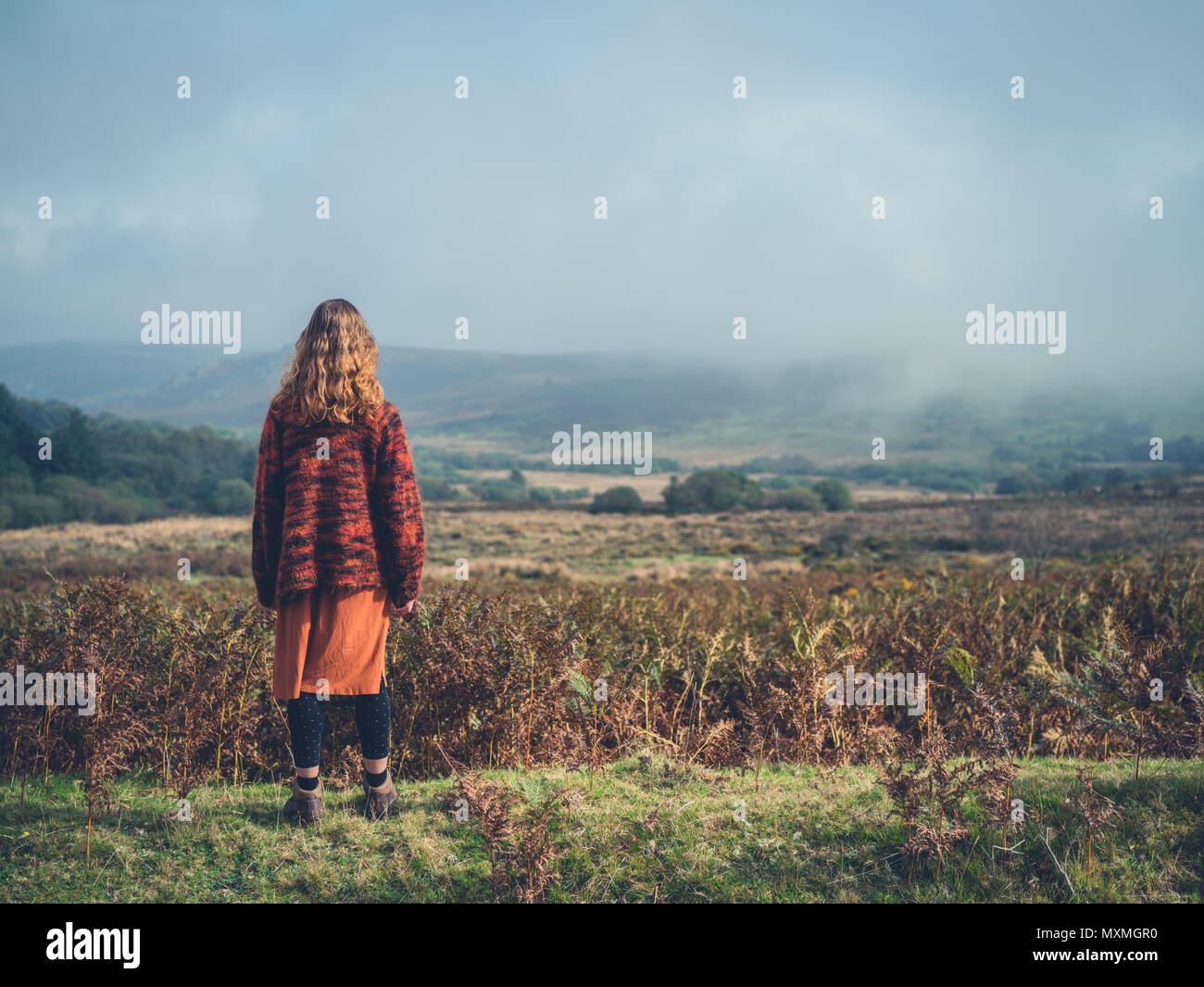 A young woman is standing on a moor in the autumn - Stock Image
