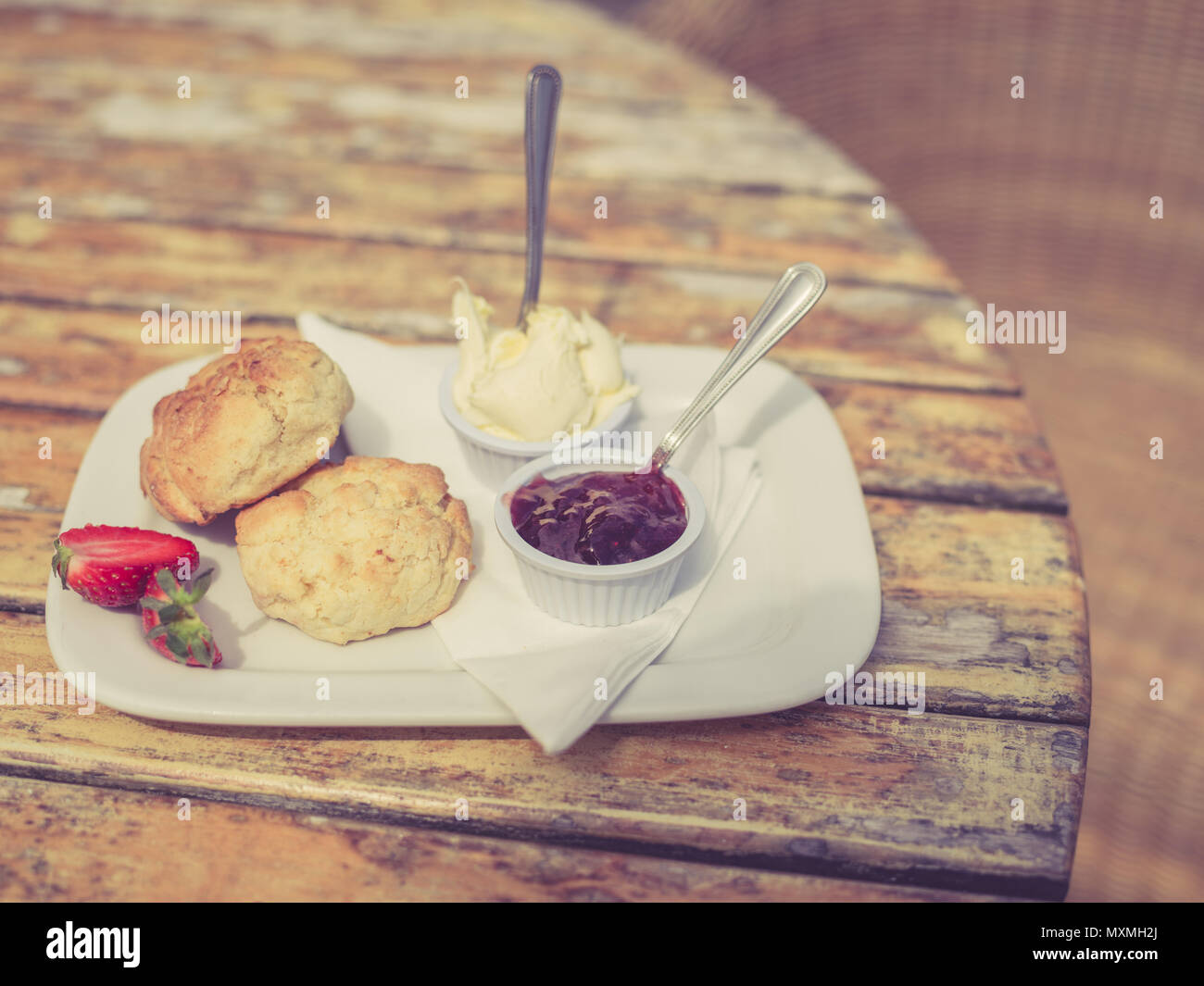 Vintage filtered shot of cream tea with scone and jam on a table - Stock Image