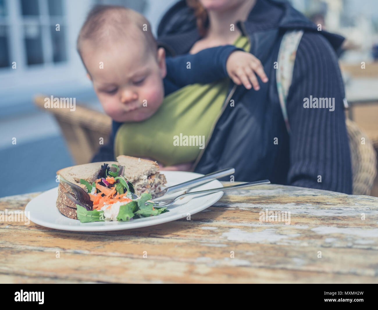 A mother with a baby in a sling is sitting at a table outside with a sandwich - Stock Image