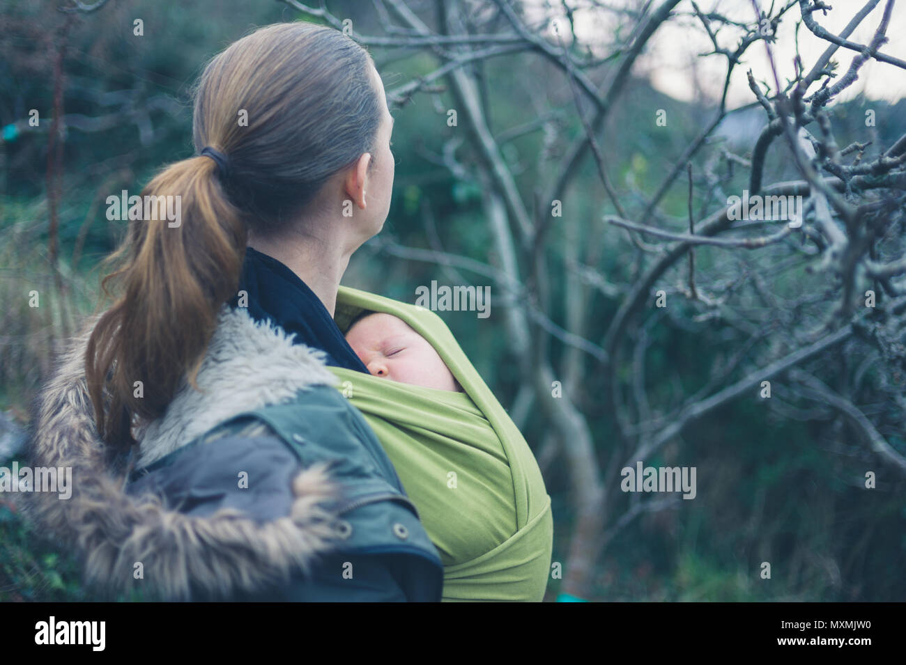 A young mother with her baby in a sling is walking in nature - Stock Image