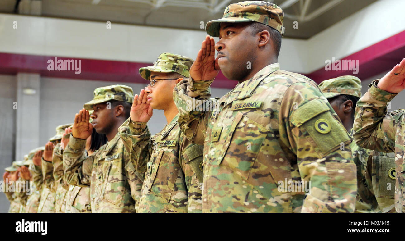 Soldiers assigned to the 14th Human Resources Sustainment Center, 1st Theater Sustainment Command, salute the U.S Flag during the National Anthem in a deployment ceremony for their unit at the at the Ritz Epps Fitness Center, Fort Bragg, N.C. The14th Human Resources Sustainment Center will be deployed for less than a year to the middle east, where their Soldiers will execute their mission of Single Sustainment Mission Command as members of 'First Team.'(U.S Army photo by Pfc. Hubert D. Delany III/22nd Mobile Public Affairs Detachment) - Stock Image