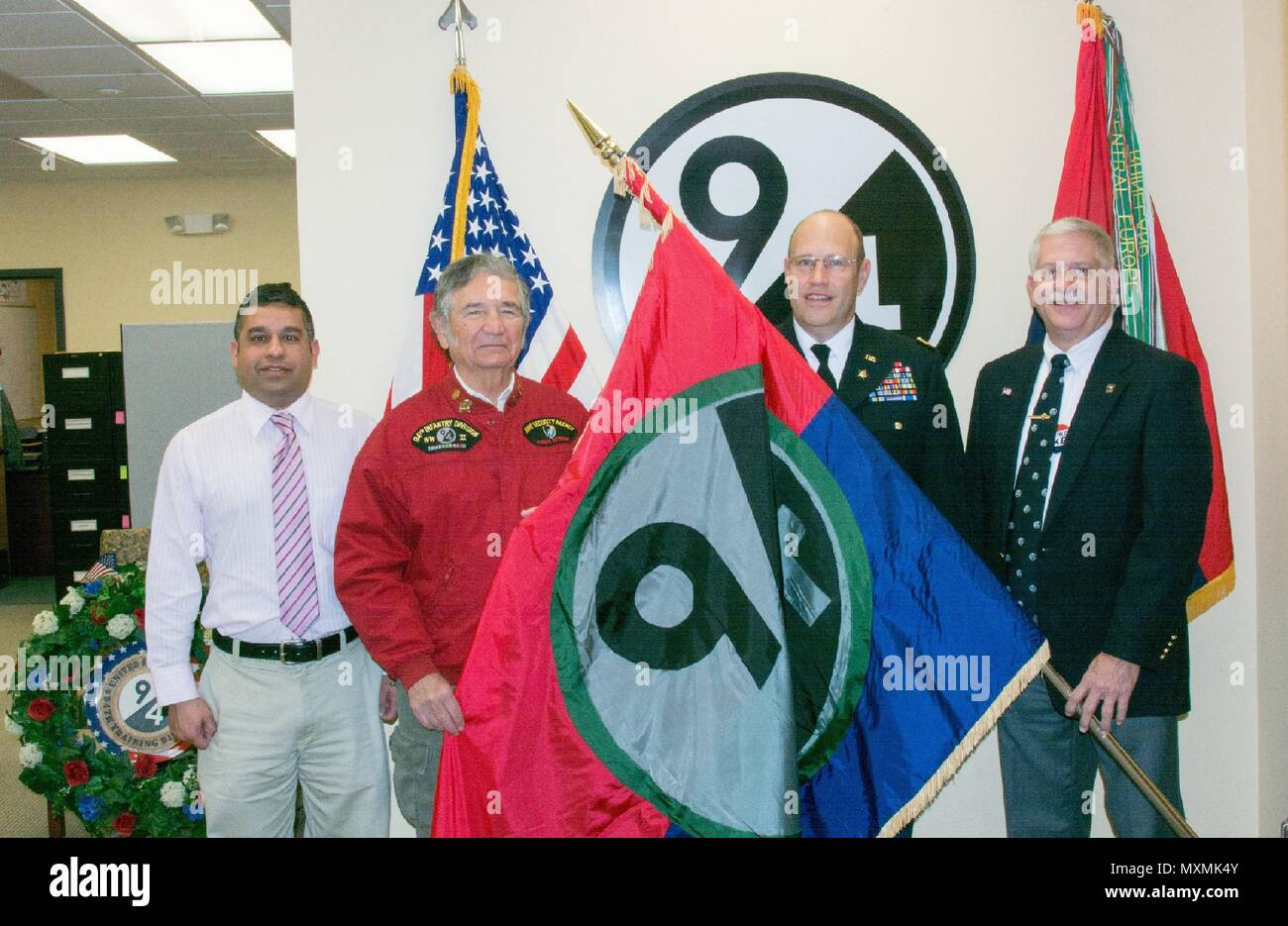 (Left to right) 94th Training Division Chief Executive Officer Vivek Kshetrapal, 94th Infantry Division Historical Society Secretary John Clyburn, 94th Training Division Assistant Division Commander Col. John Aarsen, and 94th IDHS Immediate Past President Bill Van Sant participate in the flag transfer held at Fort Lee, Virginia, Nov. 21, 2016. The 94th IDHS passed their World War II colors to the current 94th Training Division at the division's headquarters. - Stock Image