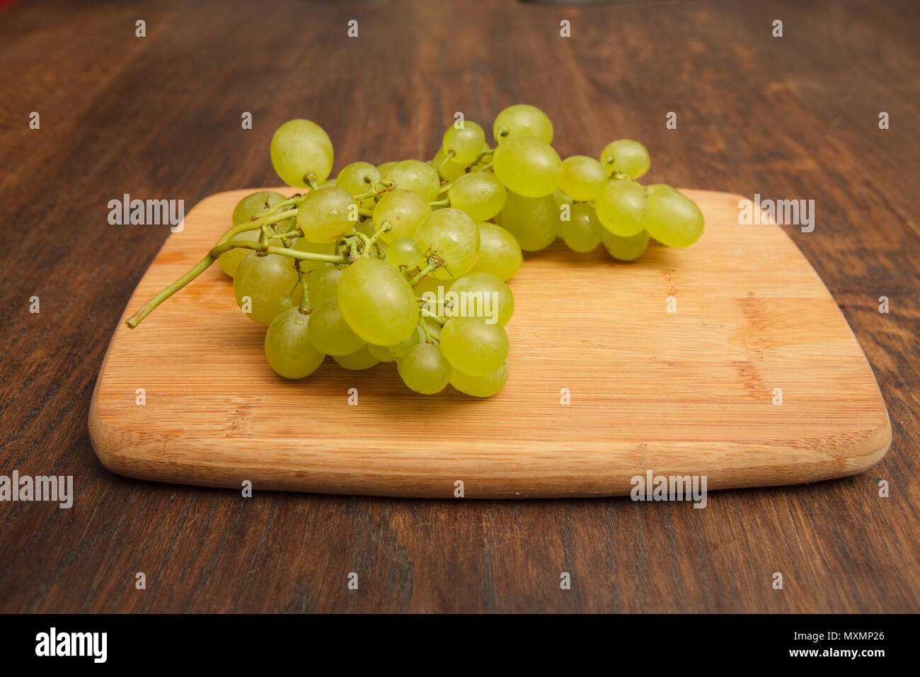 white fresh grapes on woden baord, on oak table - Stock Image