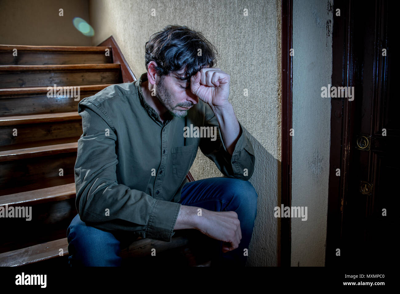 depressed latin man sitting head in hands inside in a stairwell feeling lonely and sad and stressed about work and life in a mental health concept - Stock Image