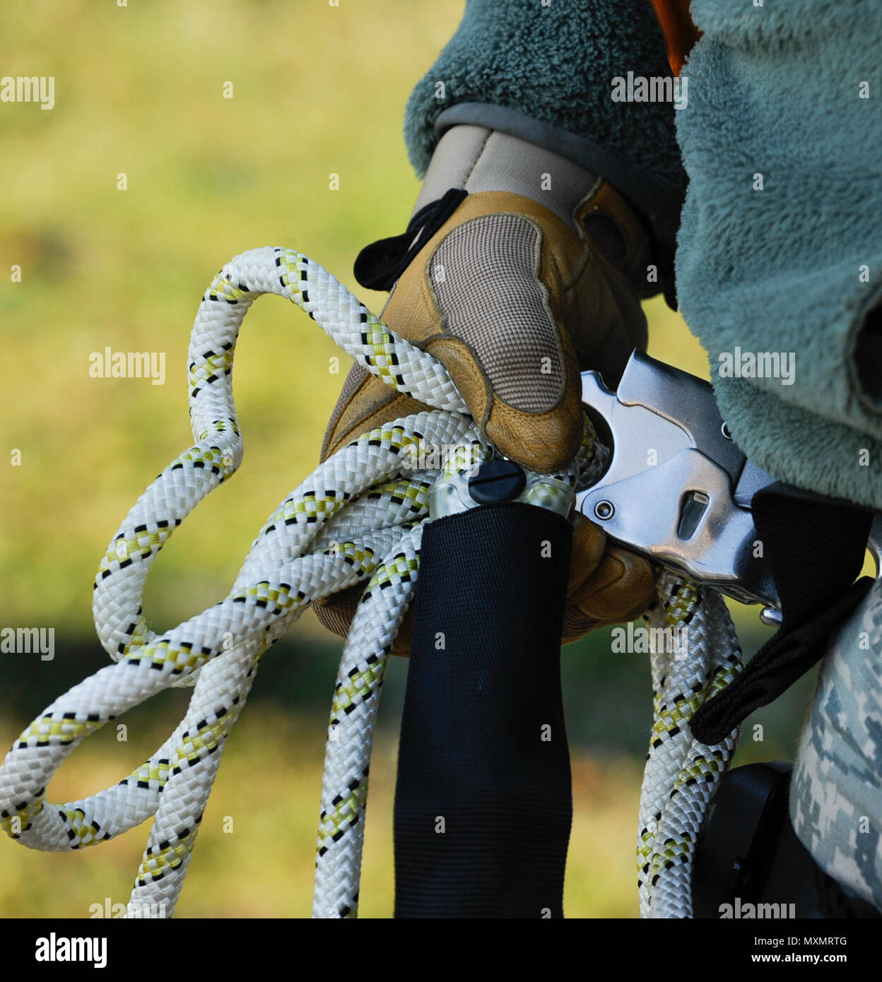 Senior Airman Mathew Godec, 86th Operations Support Squadron airfield systems technician, bundles excess rope at Ramstein Air Base, Germany, Nov. 14, 2016. This equipment is used to assist 86th OSS Airmen in climbing air traffic control radio antennas across the base to keep the airfield open and the Instrument Landing Systems in compliance with the Federal Aviation Administration and International Civil Aviation Organization standards. (U.S. Air Force photo by Airman 1st Class Savannah L. Waters) - Stock Image
