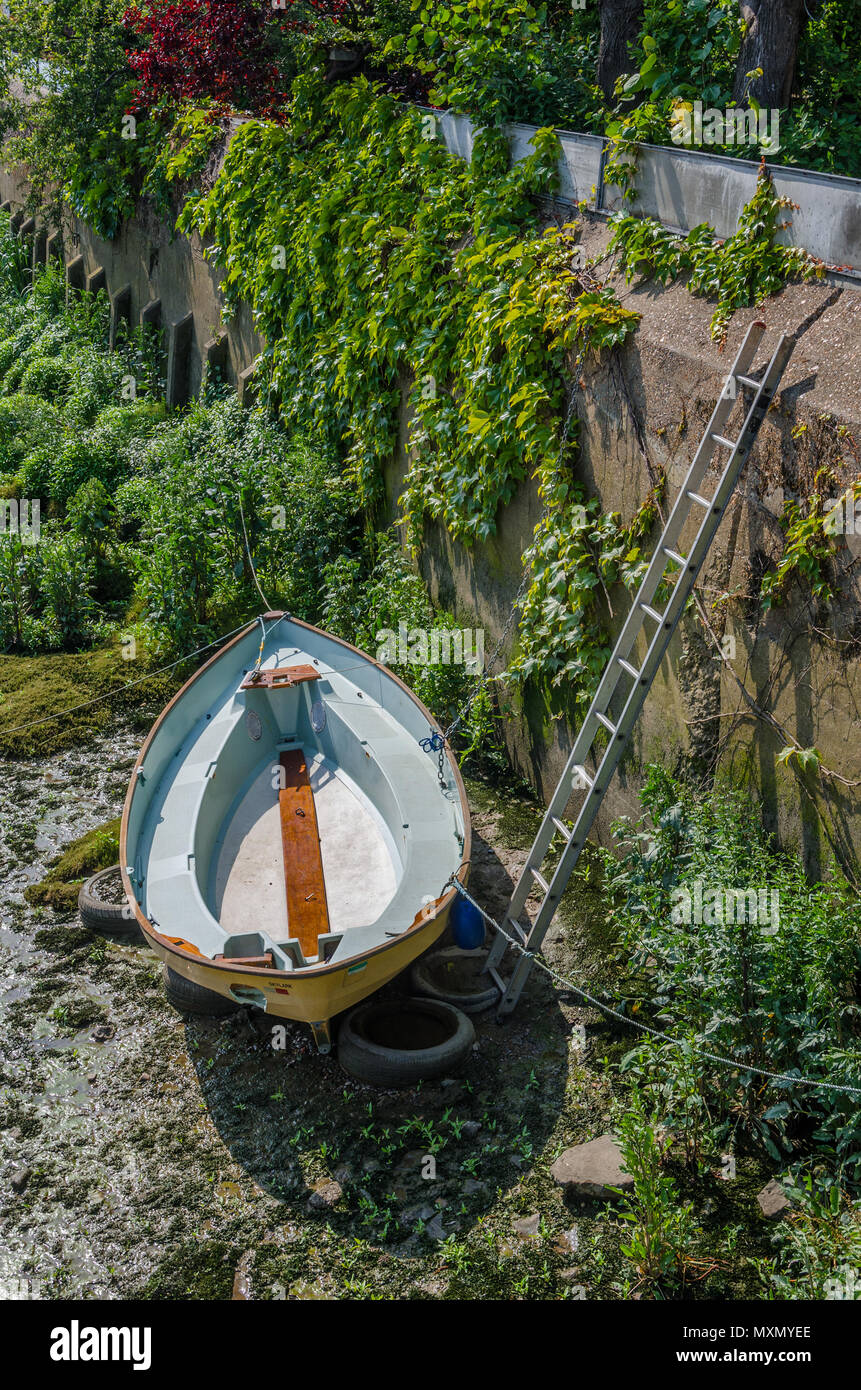 A boat is beached on the muddy river bed during low tide on The River Thames. Stock Photo