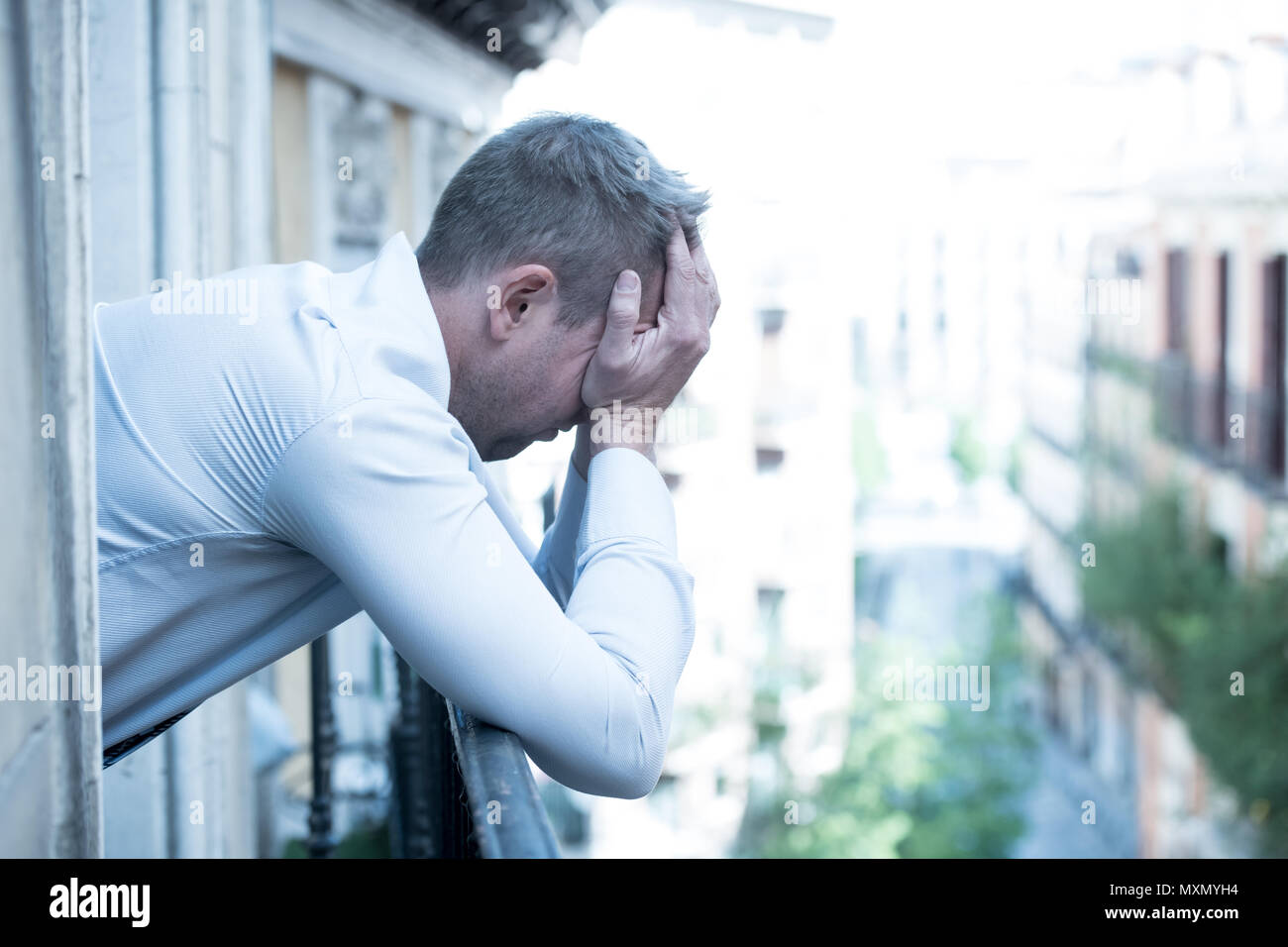 close up portrait of sad and depressed man looking out the window on a balcony at home suffering depression and felling lonely in mental health concep - Stock Image