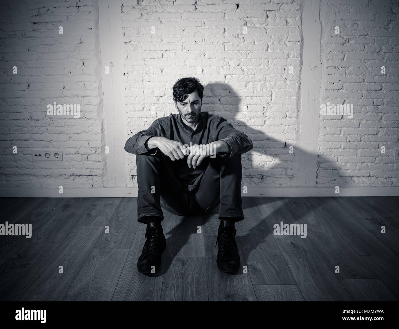Young depressed man sitting against a white wall at home with a shadow on the wall feeling miserable lonely and sad in mental health depression conce
