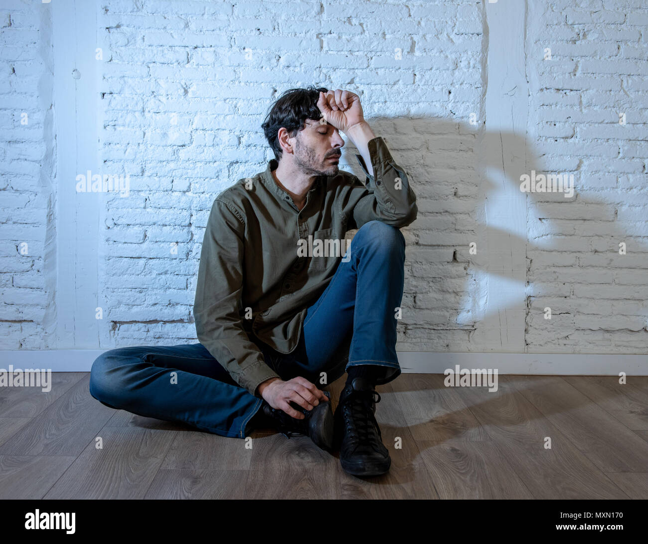 Young Depressed Man Sitting Against A White Wall At Home With A Shadow On The Wall Feeling Miserable Lonely And Sad In Mental Health Depression Conce Stock Photo Alamy