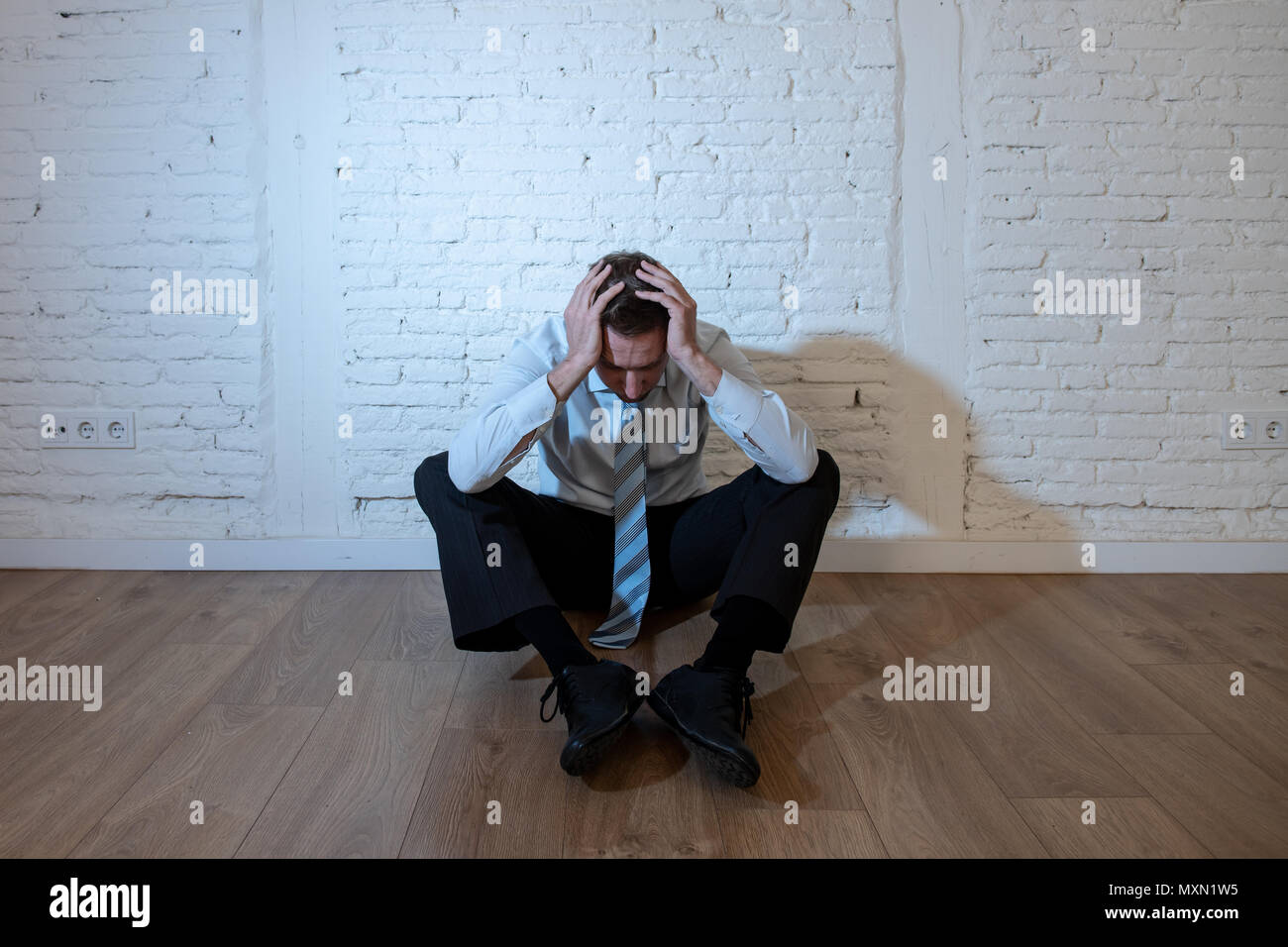 depressed business man feeling sad, lonely and suffering from anxiety leaning on a white wall at home in mental health depression concept - Stock Image