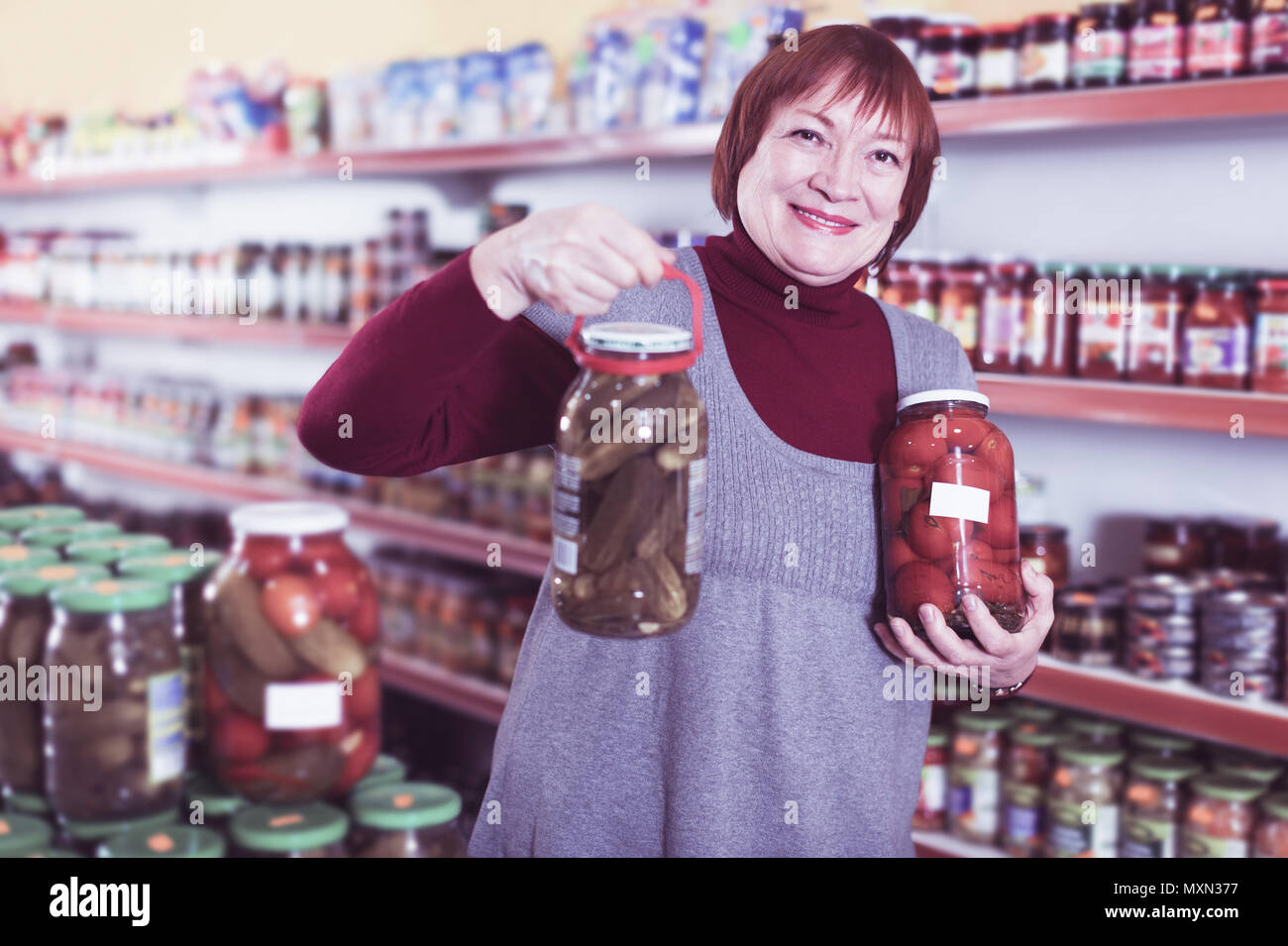 Elderly female in food shop holding preserved of cucumbers and tomatoes - Stock Image
