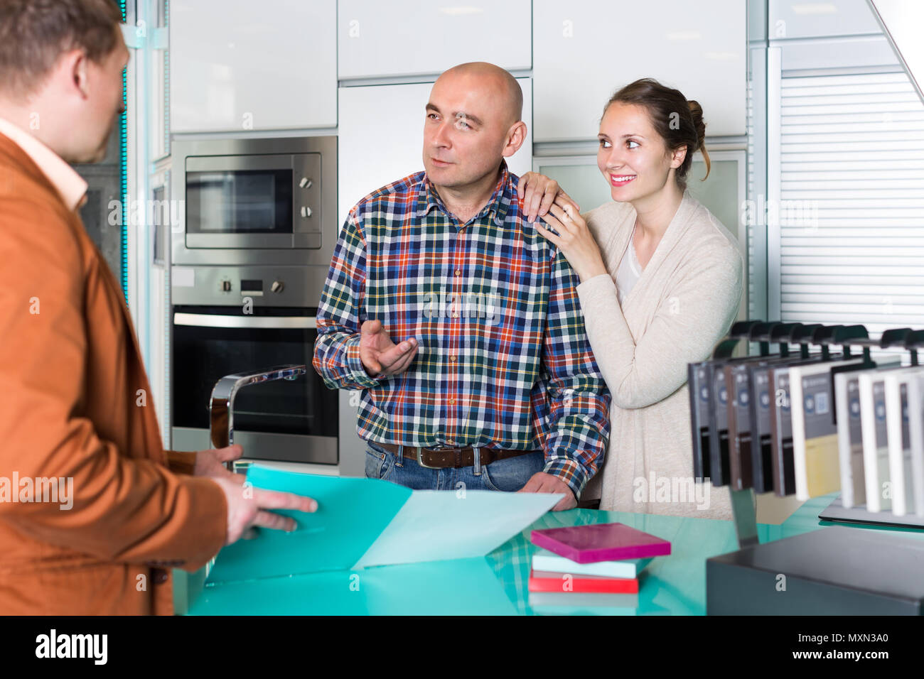 Nice seller and spouses customers at kitchen furniture workshop
