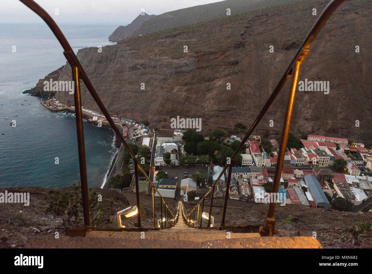 View down the 699 steps of Jacob's Ladder which climb up Ladder Hill from Jamestown, seen in the background at dusk. Ladder Hill, St Helena - Stock Image