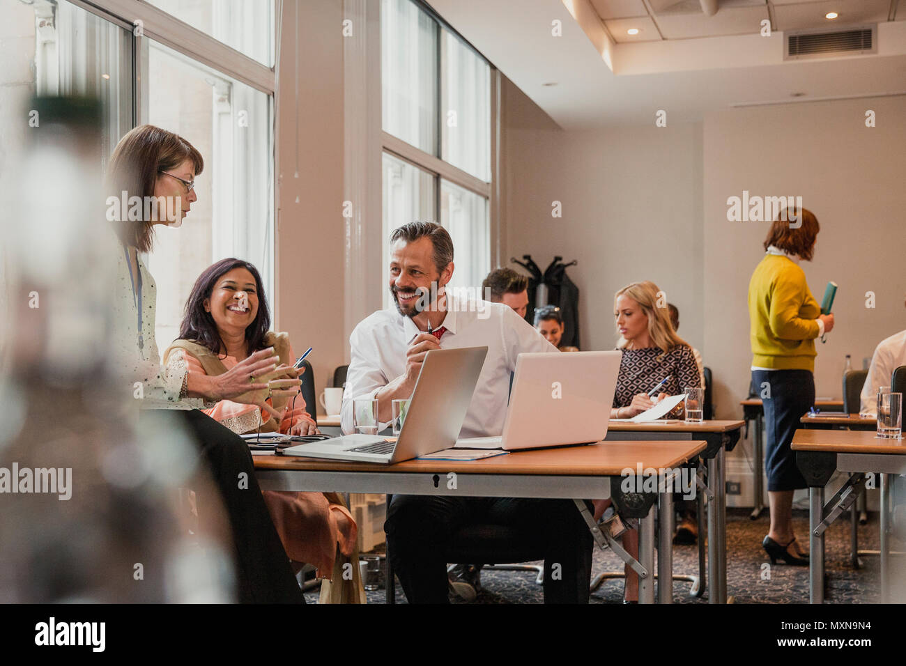 Co-workers talking and discussion information from the laptops. Having a meeting during a lunchbreak from the business conference. - Stock Image