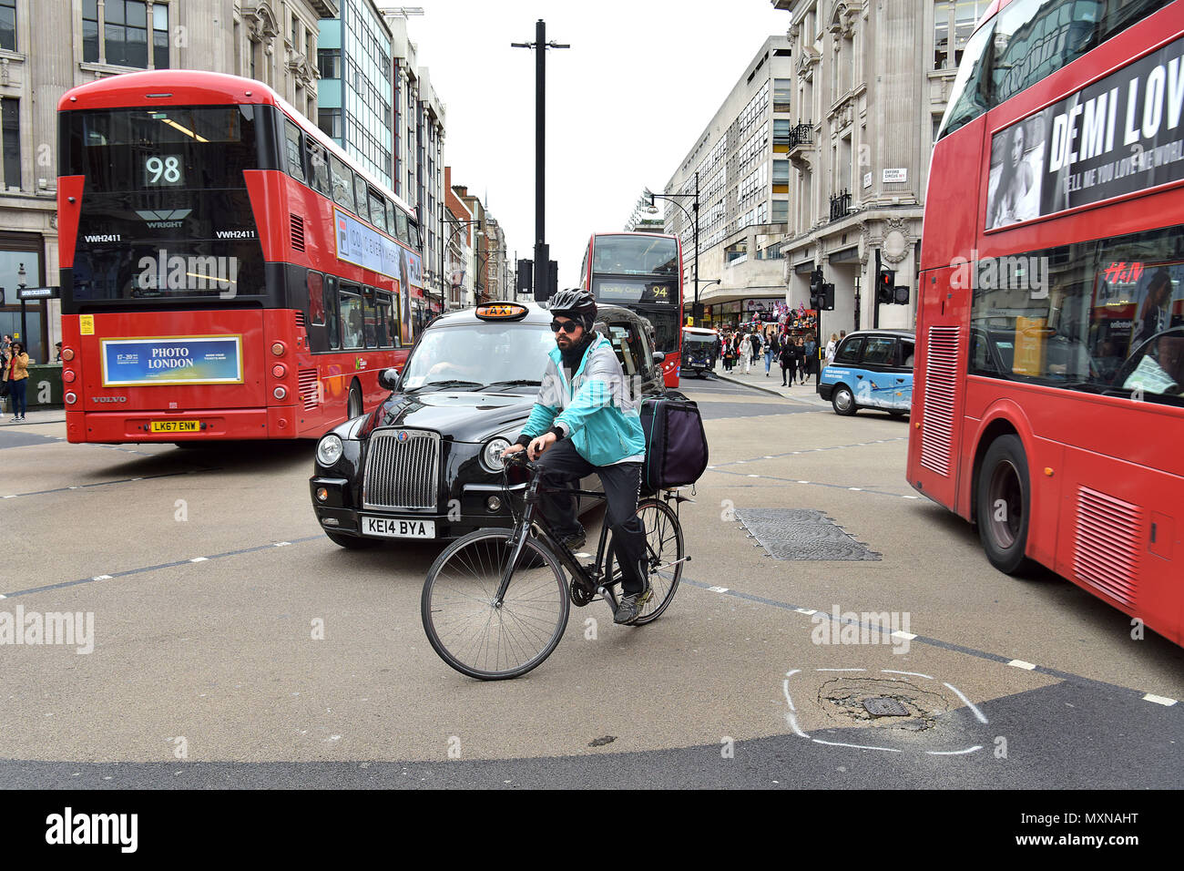 A Deliveroo delivery rider on his bicycle negotiates the Oxford Circus road junction, central London. - Stock Image