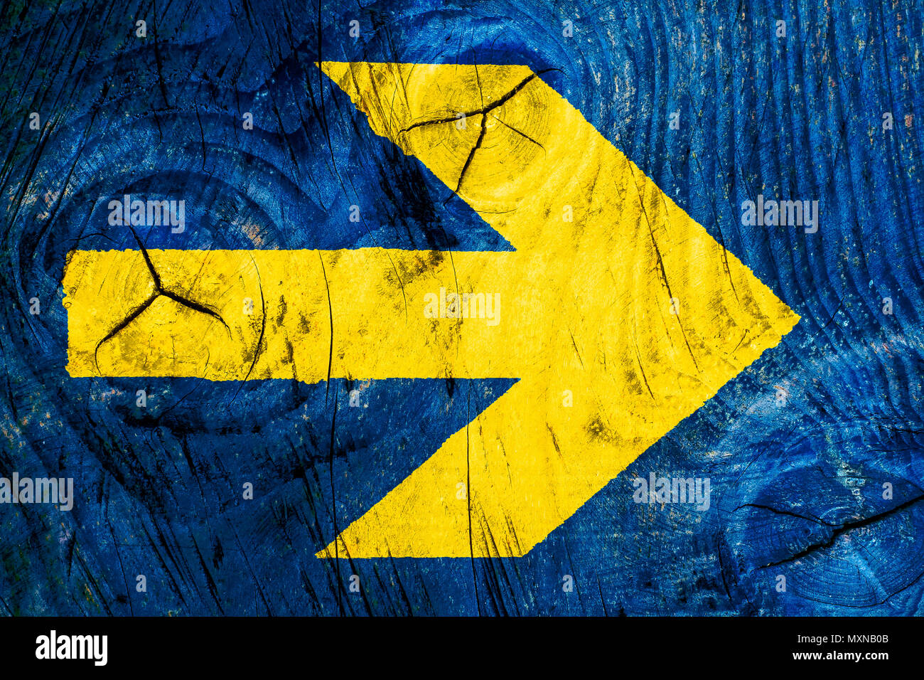 Yellow arrow direction sign over vivid bright blue color wooden wall ...