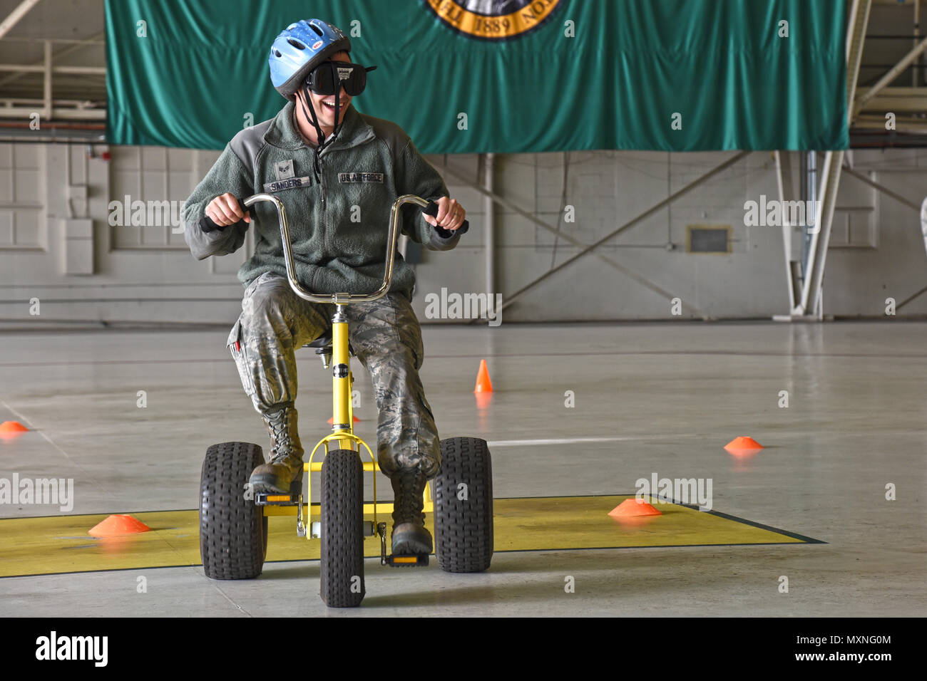 Senior Airman Edwin Sanders, 92nd Aircraft Maintenance Squadron aerospace propulsion journeyman, participates in the drunken tricycle obstacle course during the 92nd and 141st Maintenance Group Fall Olympics Nov. 15, 2016, at Fairchild Air Force Base. The obstacle course consisted of numerous gates and pathways to navigate through while wearing drunk goggles that simulated vision of having a blood alcohol content of double the legal limit. (U.S. Air Force photo/Senior Airman Mackenzie Richardson) - Stock Image