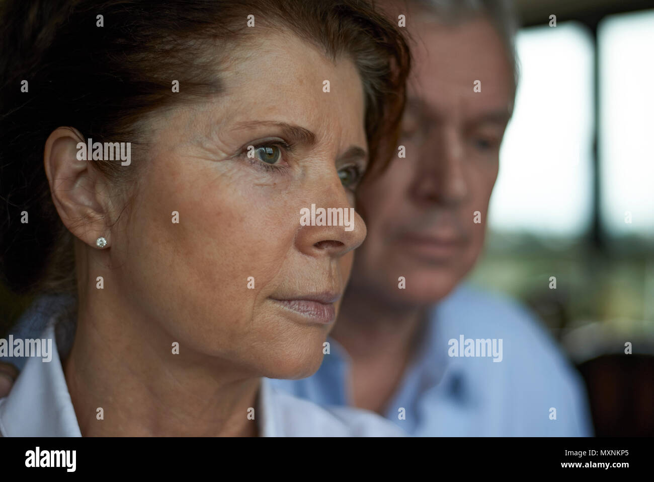 Elderly couple together art home, the husband is seen comforting his wife in a loving embrace after receiving some bad news - Stock Image
