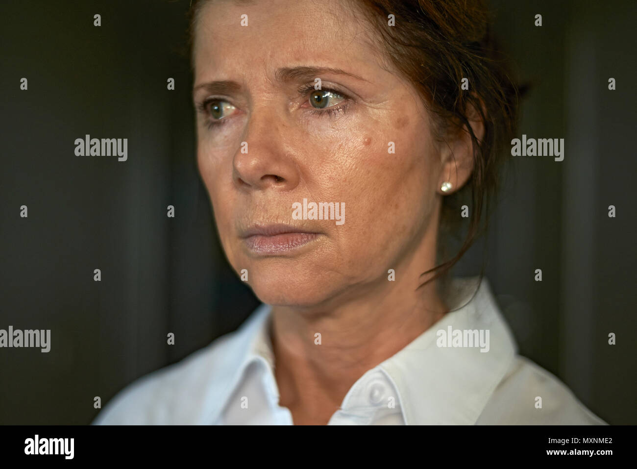 Portrait of an elderly caucasian woman looking very lost and upset with teary eyes about to cry - Stock Image