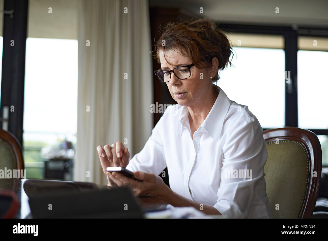 Elderly caucasian woman sitting at table in her home with a mobile phone in her hands looking very worried and upset having received bad news - Stock Image