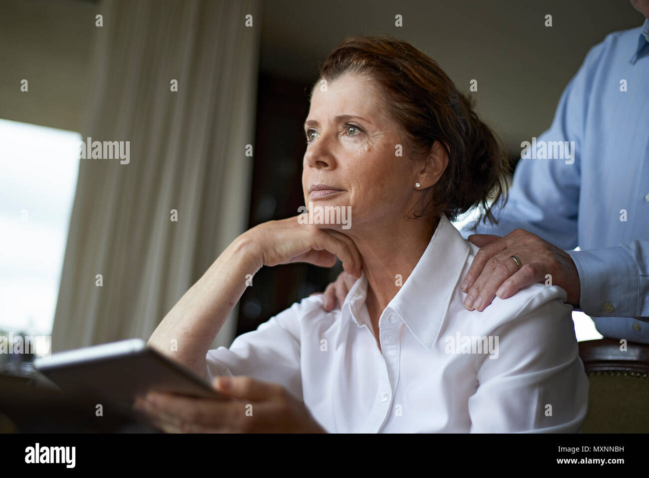 Edlery woman sitting at table at home with mobile device looking upset with her husband standing behind her to comfort her - Stock Image
