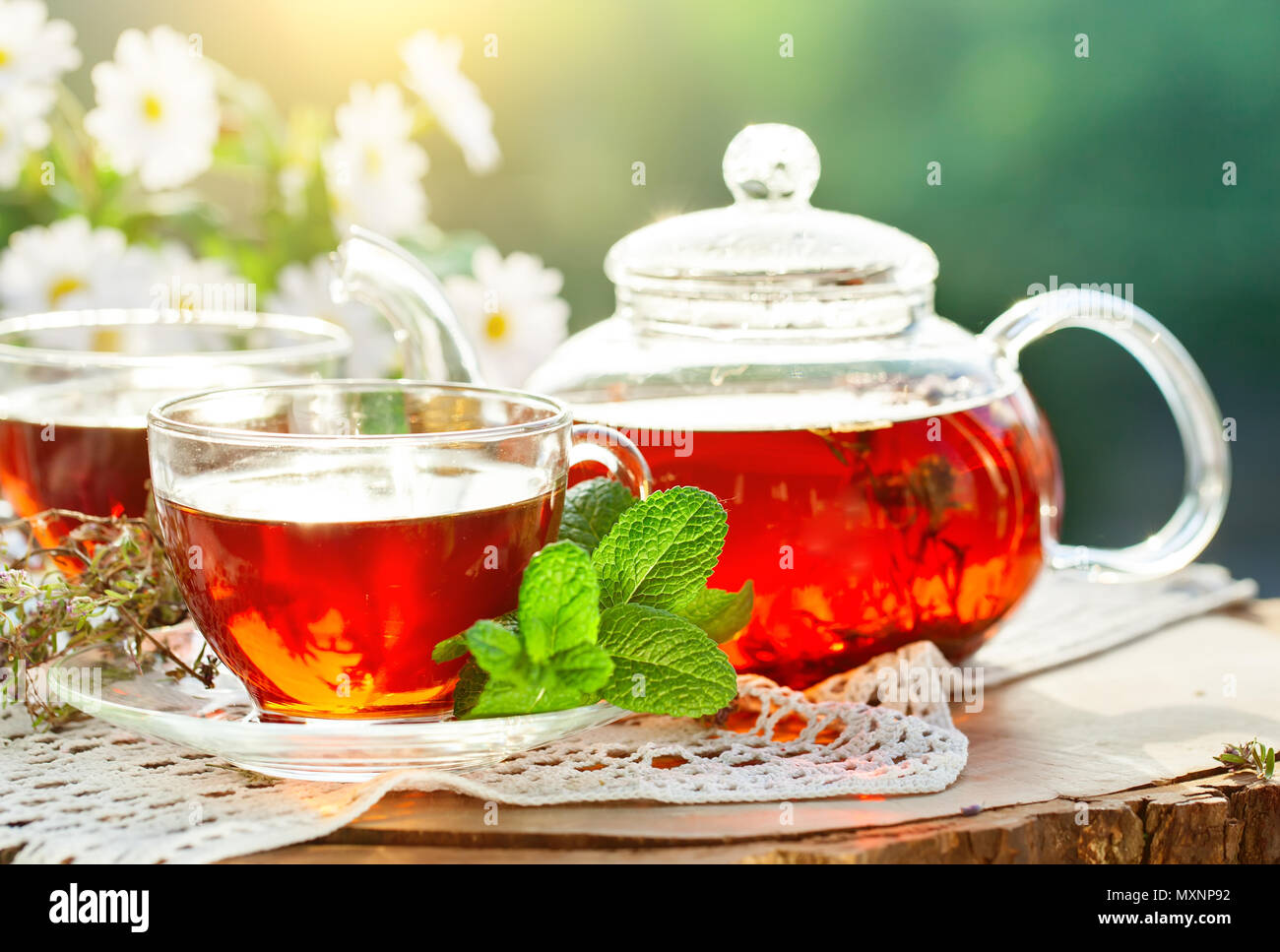 Cup with hot tea with mint and a thyme on a wooden table in a summer garden. Stock Photo