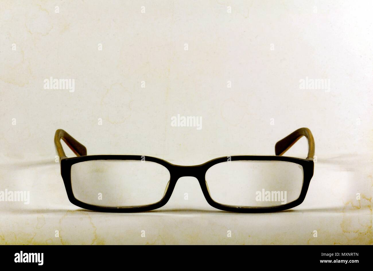 Black fashion textured reading glasses on white background. - Stock Image