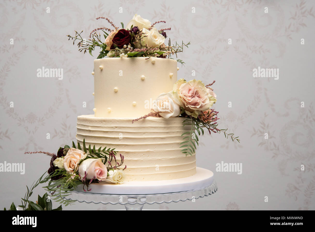 Champagne wedding cake with yellow and pink flower arrangements - Stock Image