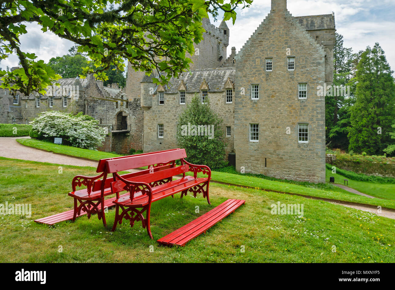 CAWDOR CASTLE NAIRN SCOTLAND RED BENCH UNDER A TREE IN FRONT OF THE BUILDING - Stock Image