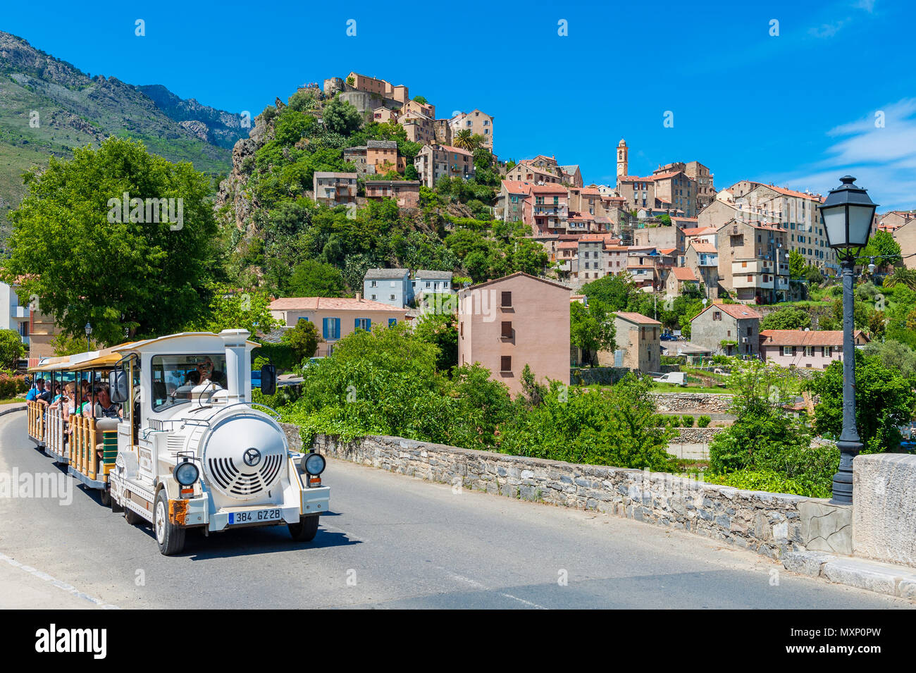 Tourist Train driving through Street in Corte, Corsica, France. Corte is best known for its Citadel and University. - Stock Image