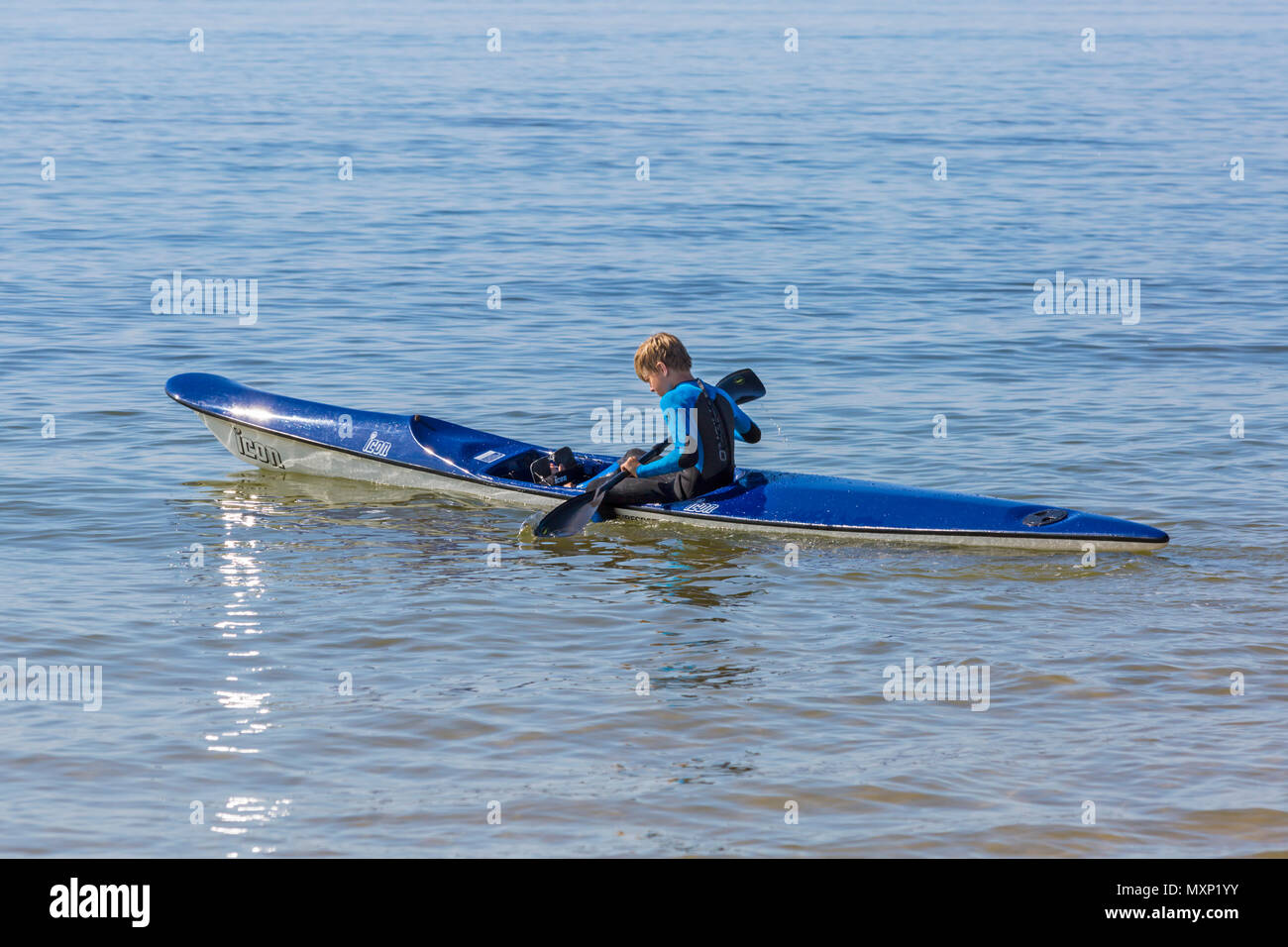 Young man in a surf ski at Branksome Chine, Poole, Dorset, England UK in June - Stock Image