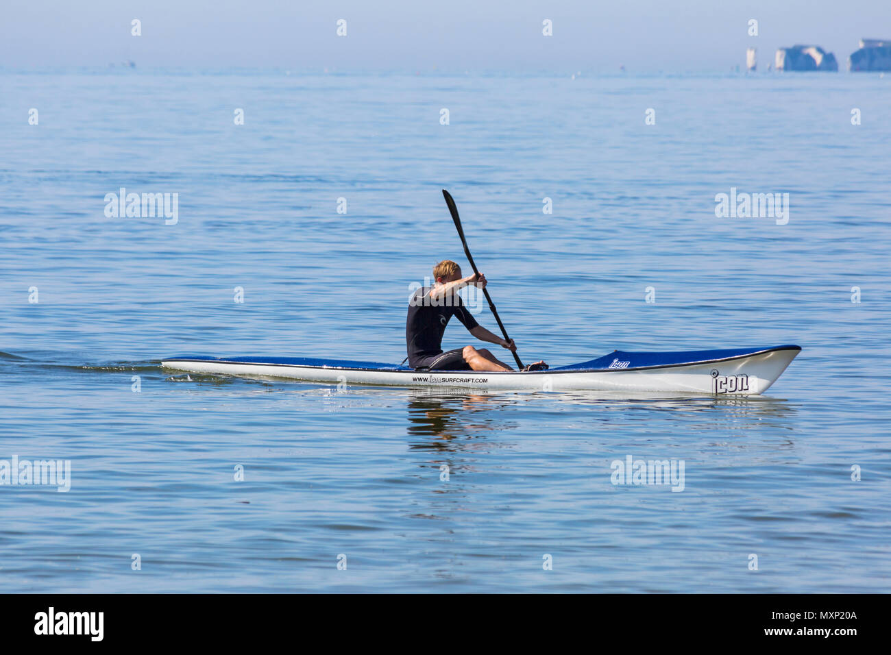 Man in a surf ski at Branksome Chine, Poole, Dorset, England UK in June - Stock Image