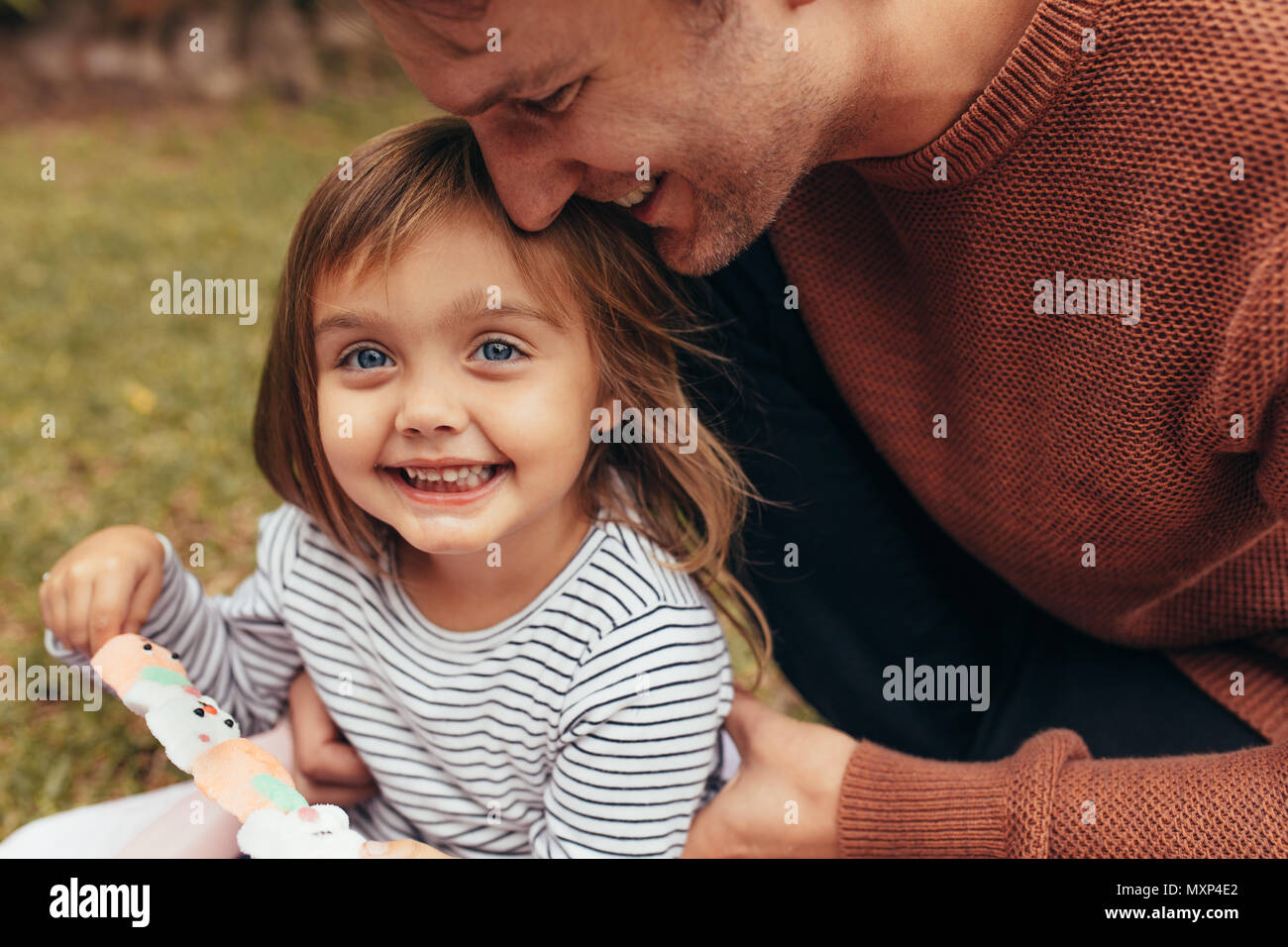 Smiling girl sitting with her father outdoors holding a sugar candy stick. Father and daughter spending time together eating sugar candy. - Stock Image