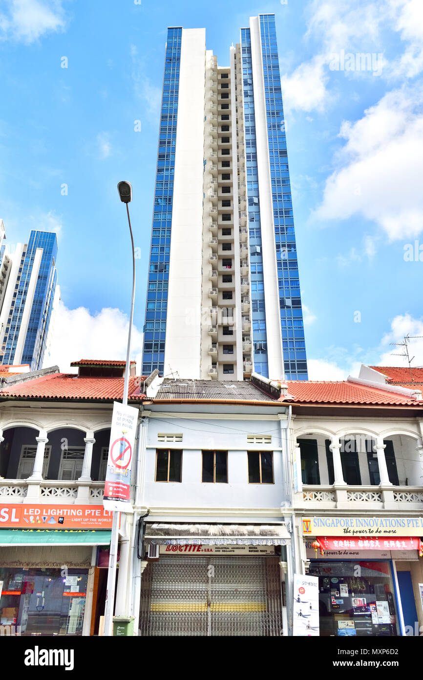 Singapore. Along Jalan Besar Road, rows of shop houses with colonial era design line the road. Behind, a tall modern condominium rises into the sky. Stock Photo