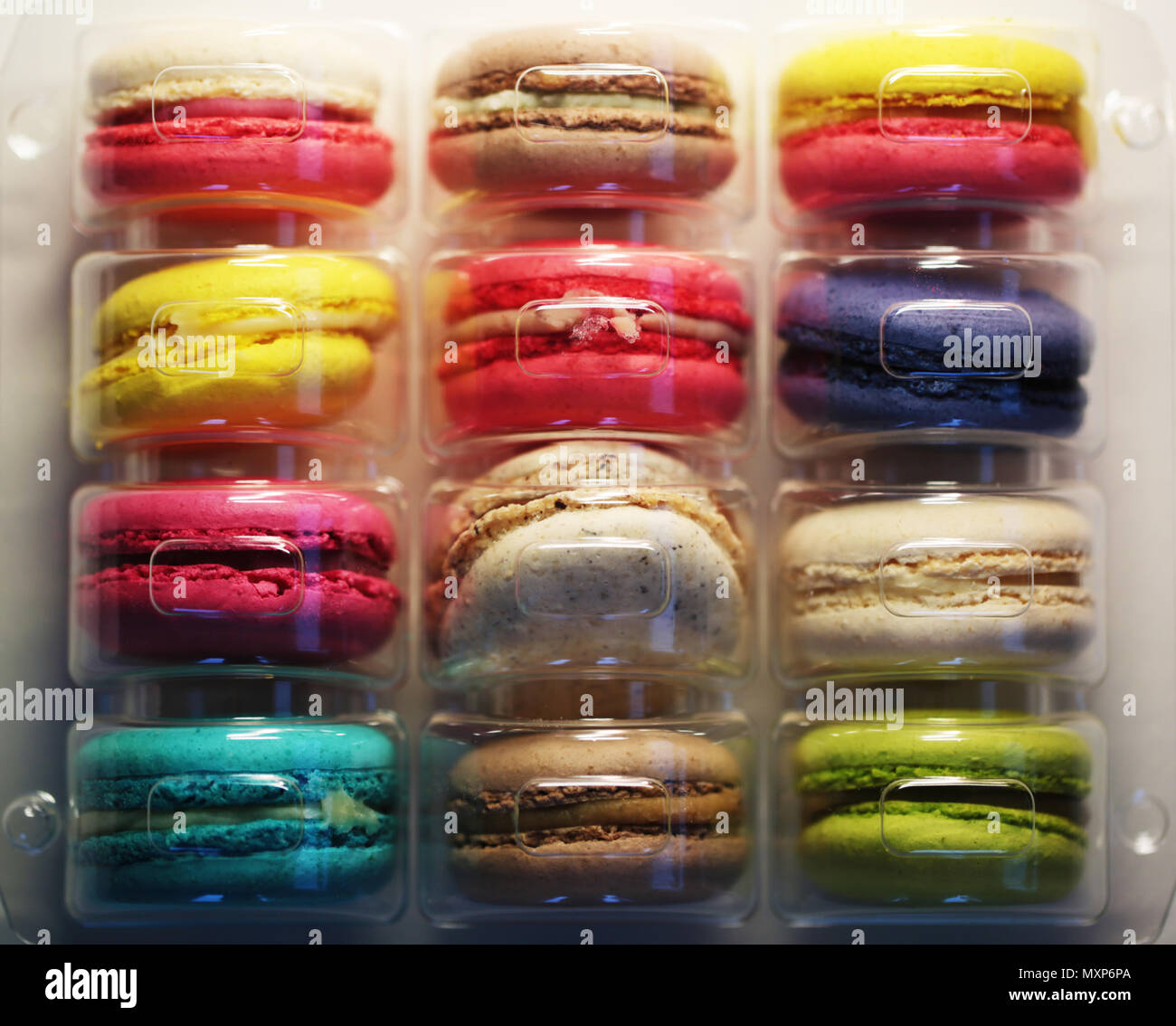Macaroons of different colors packed in plastic bag - Stock Image